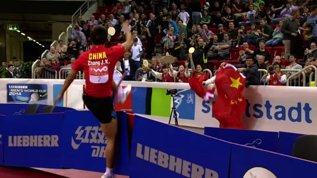 Chinese table tennis player Zhang Jike destroys two advertising boards in celebration after regaining his world title at the 2014 World Cup in Dusseldorf, Germany
