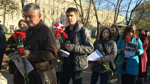 People queue to lay flower at a memorial for victims of Soviet-era political repression