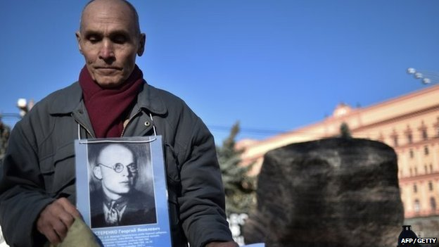 A man holds his father's portrait near the memorial to the victims of Soviet-era political repression, the Solovky Stone monument, on Lubyanka Square in Moscow, on October 29, 2014