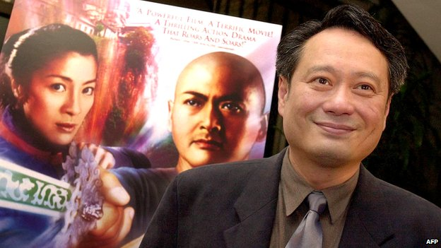Director Ang Lee poses next to a poster for his film Crouching Tiger, Hidden Dragon