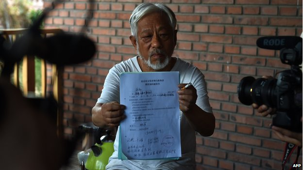 Beijing Independent Film Festival organiser Li Xianting displays a document issued by police following his release