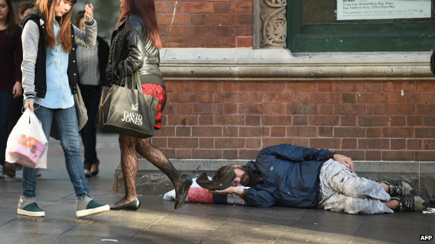 A homeless man holds out his cap for money in Sydney's Central Business District - 10 July 2014