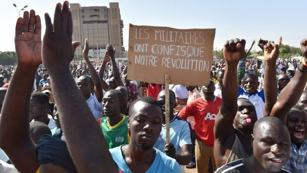 """A man holds up a placard that reads """"the military has confiscated our revolution"""", during a protest at the Place de la Nation in Ouagadougou, November 2"""