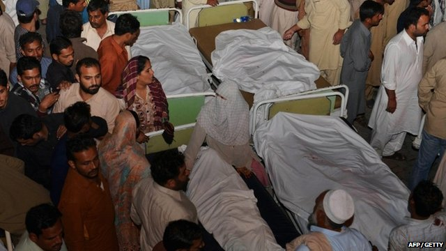 Pakistani relatives gather around the bodies of blast victims after a suicide bomb attack near the Wagah border