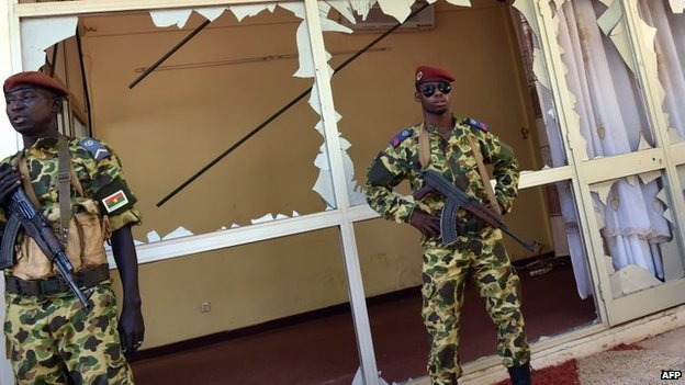 Troops stand guard outside the national television headquarters in Ouagadougou on November 2