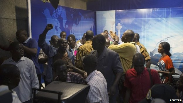 People gather at the podium of the state TV headquarters in Ouagadougou, Burkina Faso, 2 November 2014