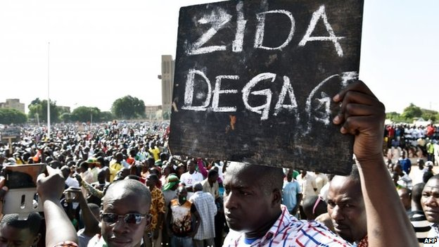 "A man holds up a placard that reads in French, ""Zida get out"", referring to Isaac Zida, a high-ranking officer named by the military to lead the country's transition, during a protest at the Place de la Nation in Burkina Faso's capital Ouagadougou, 2 November 2014"