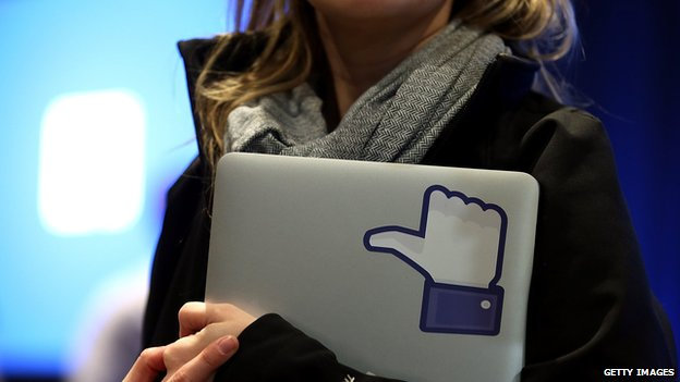 Woman holds laptop with thumbs-up 'like' logo