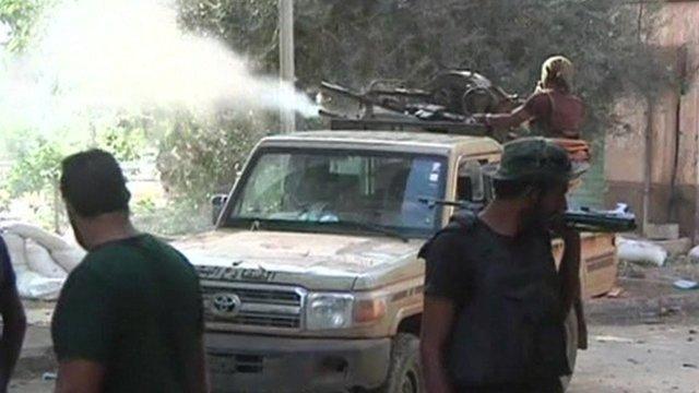 Man firing gun from roof of vehicle