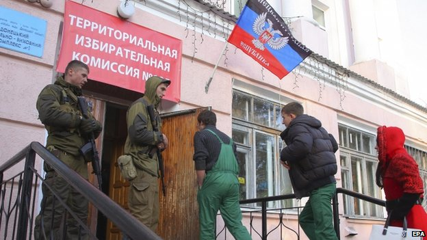 Armed security men guard a polling station during the elections in Donetsk