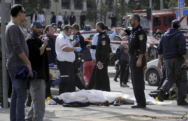 The body of a Palestinian driver who rammed his vehicle into a crowded train platform lies at the scene in Jerusalem, Wednesday, Nov. 5 , 2014