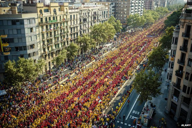 Tens of thousands of Catalans in red and yellow shirts waving independence flags (Esteladas) gather in Barcelona's Gran Via on Catalonia's national day to form a giant 'V'