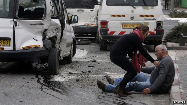 A wounded man sits on the street after an attack by the Palestinian motorist in Jerusalem (5 November 2014)