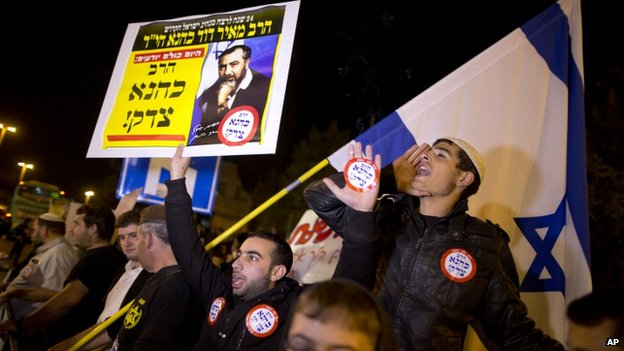 Israeli right wing activists demonstrate at the site where a Palestinian man rammed a minivan into a crowded train stop in Jerusalem (5 November 2014)