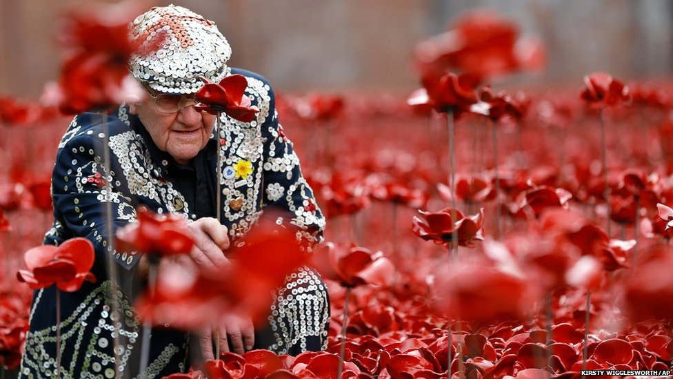 Harry Mayhead, Pearly King of Bow Bells who served in Egypt and France for the Royal Army Service Corp. in World War Two, plants poppies at the Tower of London (19 September2014)