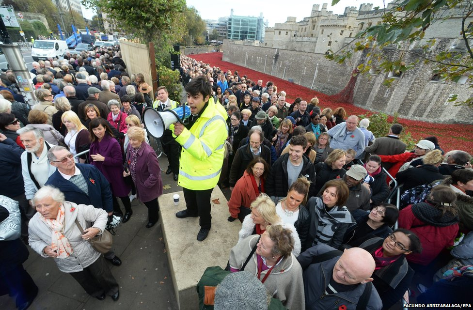 A steward instructs record numbers of visitors at the Tower of London (6 November2014)