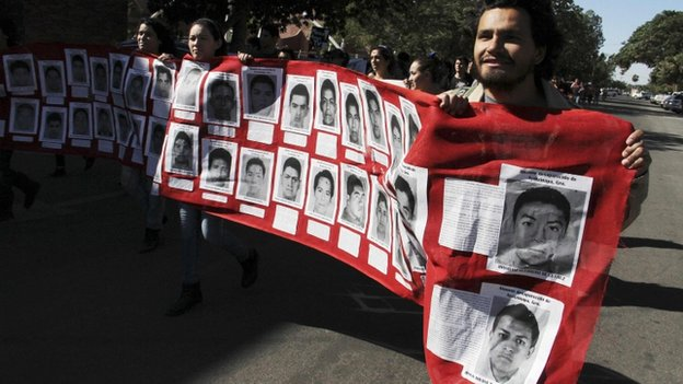 Students carry a banner with photographs of missing students. 5 Nov 2014