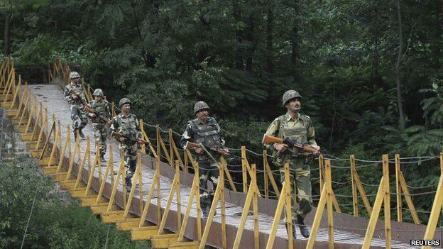 Indian Border Security Force (BSF) soldiers patrol over a footbridge near the Line of Control that divides Kashmir between India and Pakistan