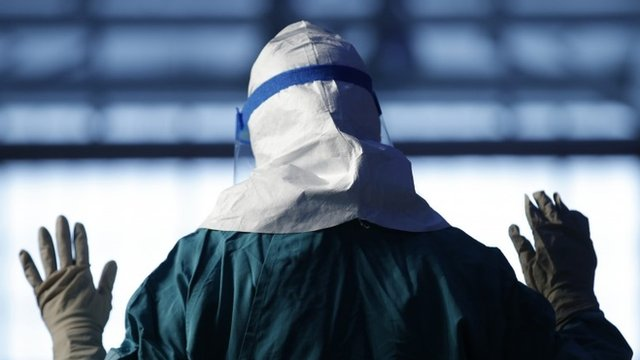 A file picture of a nurse demonstrating putting on personal protective equipment during an Ebola educational session in New York
