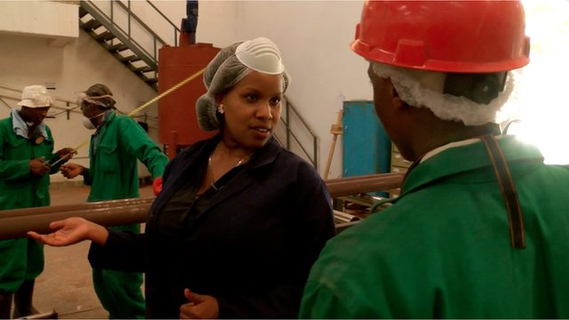 Lorna Rutto speaking to a man in a factory