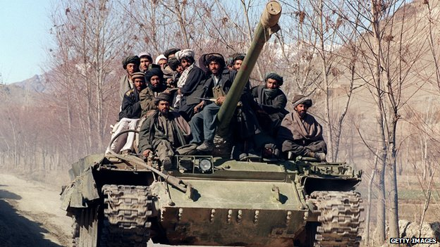 A group of Islamic militants, members of the Afghan religious Taliban militia, move toward the front line on a tank, near Kabul, on February 18, 1995
