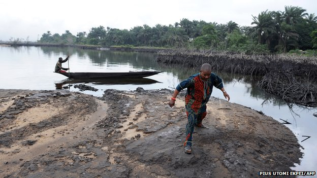 A man walks on slippery spilled crude oil on the shores and in the waters of the Niger Delta swamps of Bodo, a village in the famous Nigerian oil-producing Ogoniland, which hosts the Shell Petroleum Development Company (SPDC) in Nigeria's Rivers State on June 24, 2010.