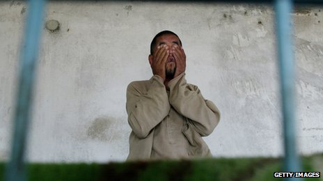 A resident of Kabul's 15 patient men's mental institution, sits in his bed October 15, 2002