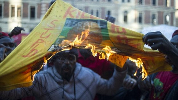 Economic Freedom fighters members burn a T-shirt of the South African ruling party African National Congress (ANC), outside the Gauteng Legislature building on 22 July 2014 in Johannesburg, South Africa