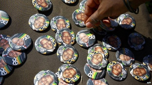 Badges showing the portraits of former South African president Nelson Mandela and current South African president Jacob Zuma with the logo of ruling African National Congress (ANC) party are sold during a march organised by the Congress of South African Trade Unions (Cosatu) to support the ruling ANC party in Durban, on 26 April 2014