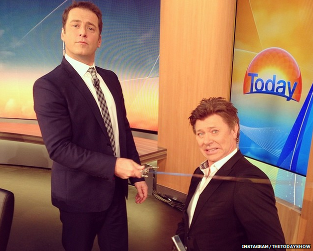Karl Stefanovic wearing the blue suit, knighting someone with a sword