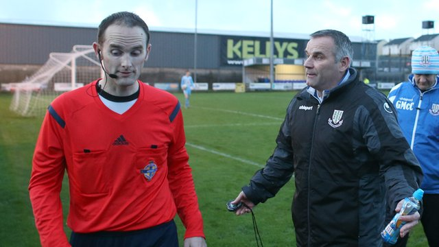 Ballymena manager Glenn Ferguson talks to referee Evan Boyce after the game was halted for 15 minutes due to floodlight problems