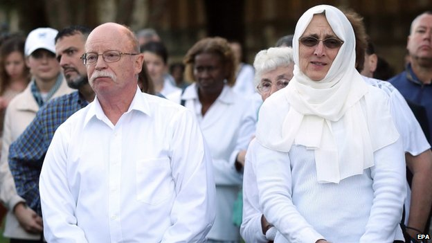 Ed (L) and Paula Kassig listen to a speaker during a prayer vigil for their son in October