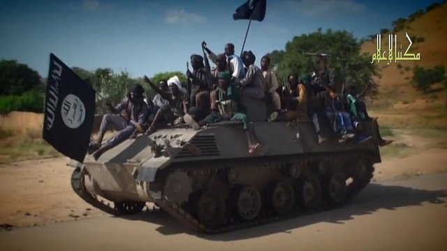 A screengrab taken on November 9, 2014 from a Boko Haram video released by the Nigerian Islamist extremist group Boko Haram and obtained by AFP shows Boko Haram fighters parading on a tank in an unidentified town