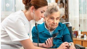 An elderly lady in a wheelchair has her pulse taken by a nurse.