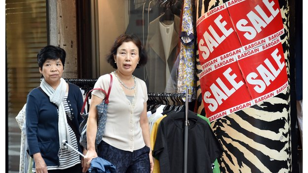 People walk past clothes displayed outside a shop in Tokyo on August 29, 2014.