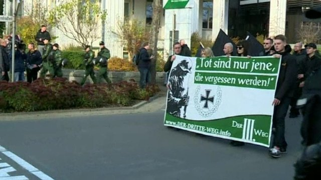 Neo-Nazis marching and carrying a banner