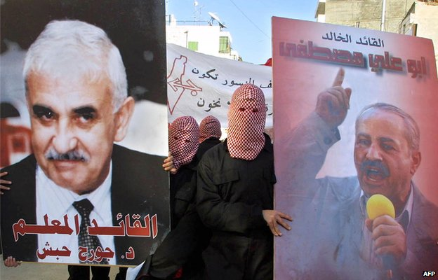 PFLP supporters hold up posters of George Habash (left) and Abu Ali Mustafa (right) in Ramallah in December 2001
