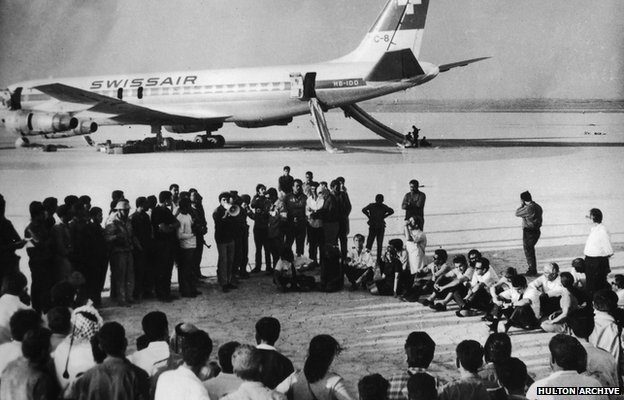 Hostages from three hijacked aircraft attend a new conference by the Popular Front for the Liberation of Palestine in the Jordanian desert, in front of a Swissair passenger plane (September 1970)