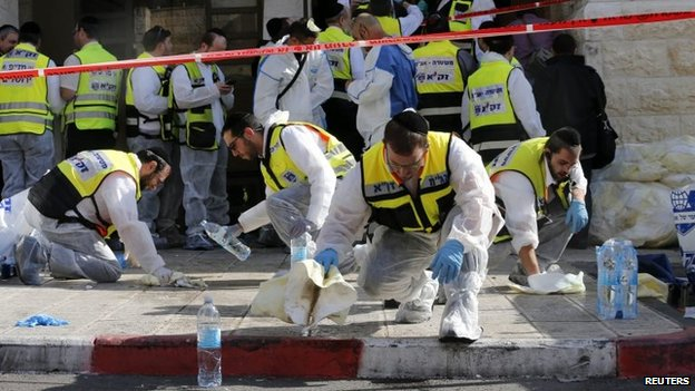 Members of the Israeli Zaka emergency response team clean blood from the scene of an attack at a Jerusalem synagogue on 18 November 2014