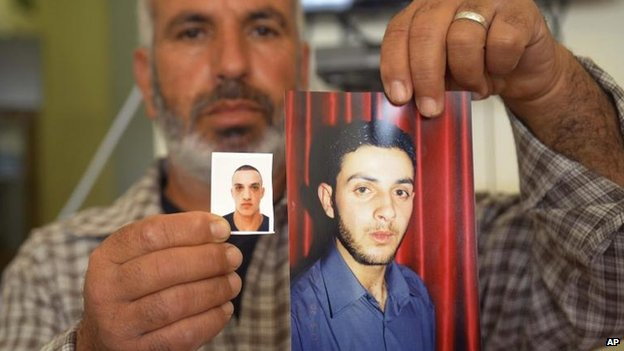 A relative with photos of Uday (left) and Ghassan Abu Jamal, 18 Nov