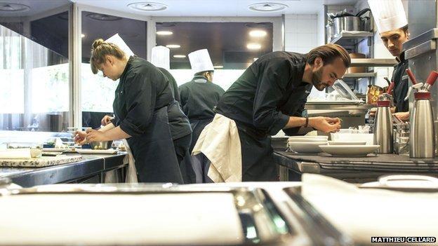 French star TV chef Cyril Lignac (R) at his restaurant Le Quinzieme in Paris