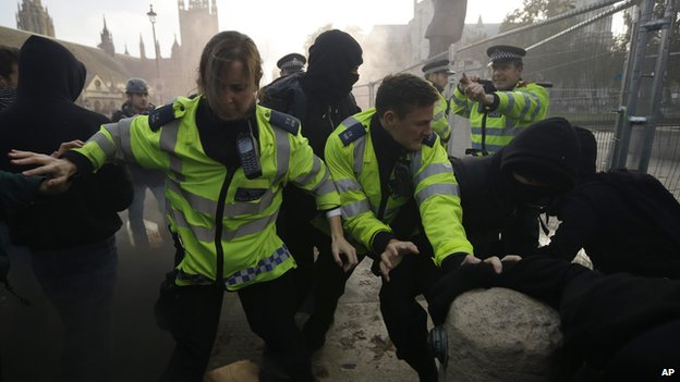 British police officers and students clash on Parliament Square during a protest against university tuition fees