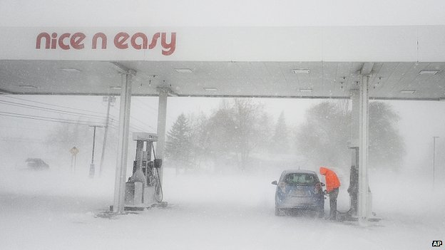 A man puts gas in his tank as snow falls at a gas station near Brownville, New York on 18 November 2014