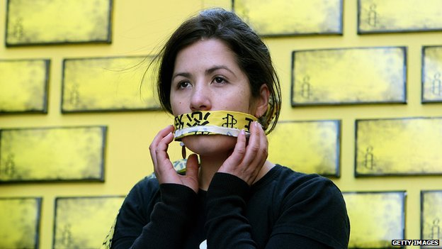 An Amnesty International activist covers her mouth as part of a campaign to end internet censorship in China