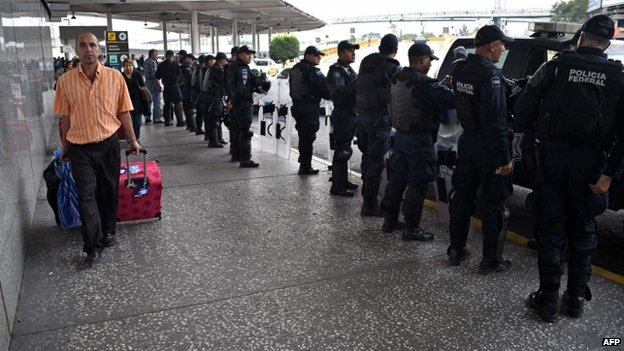 A traveller arrives at the departure terminal of Mexico City's international airport guarded by Federal Police personnel in riot gear on 20 November 2014.