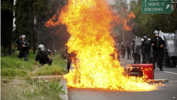 A motorcycle burns after protesters threw molotov cocktails at riot police near the airport in Mexico Cityon 20 November 2014.