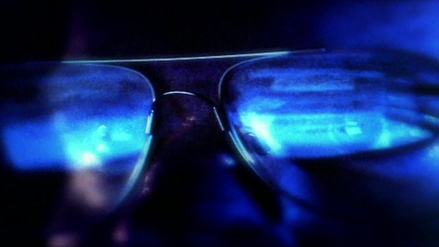 Computer screen reflected in a man's spectacles.