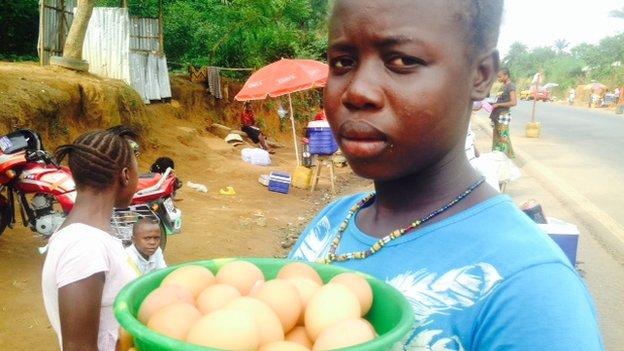 A woman sells eggs at a checkpoint, Sierra Leone, 21 November 2014
