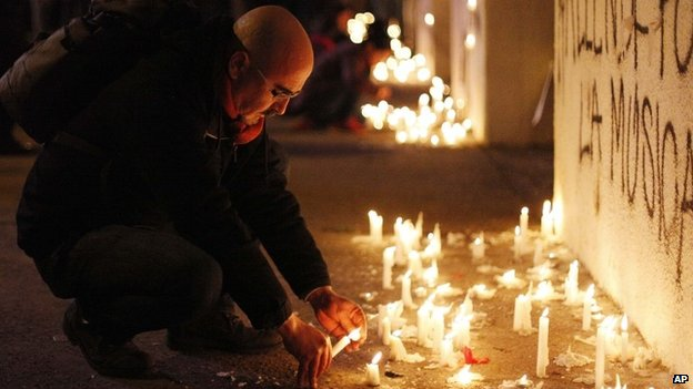 A man lights a candle in the front of the National Stadium during a candlelight vigil marking the 41st anniversary of the military coup that ousted the late President Salvador Allende, in Santiago, Chile