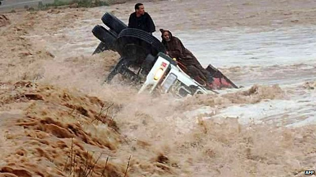 Drivers and a truck are stranded in flood waters on 22 November 2014 in the southern region of Ouarzazate in Morocco
